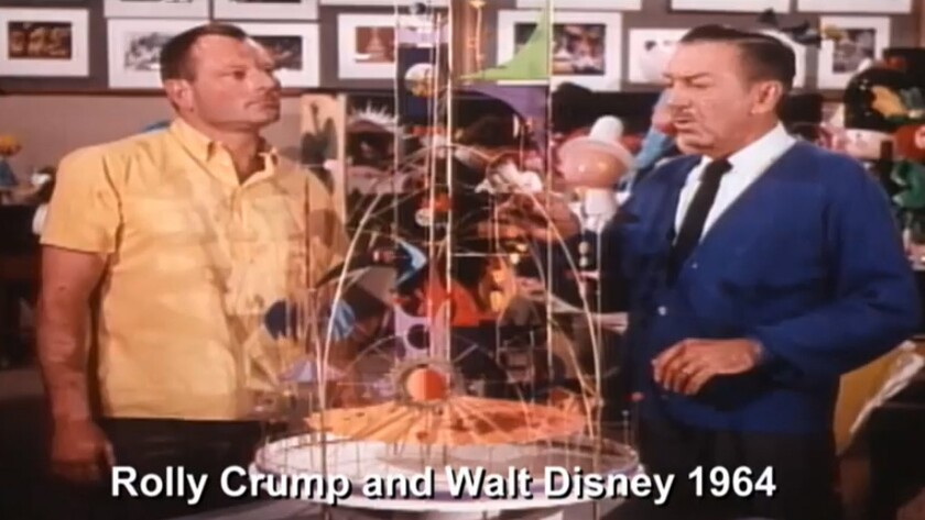 Imagineer Rolly Crump, left, and Walt Disney look over a Tower of the Four Winds model during a 1964 television broadcast.