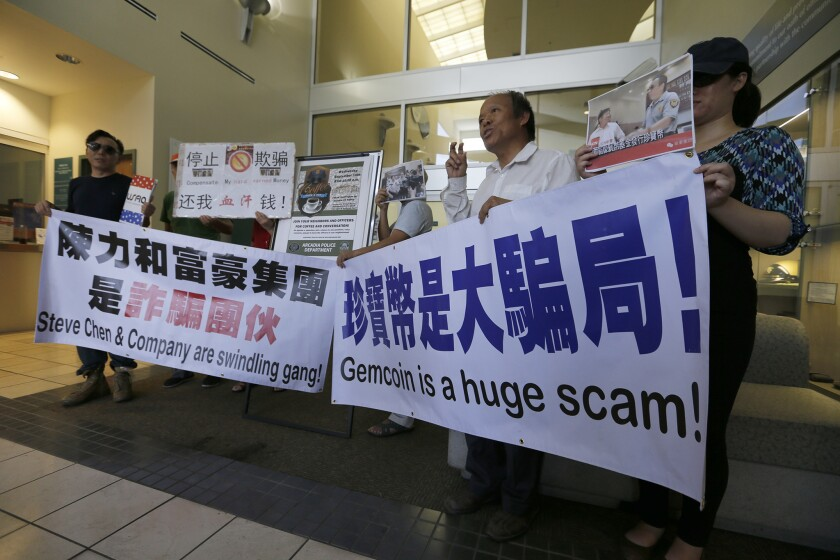 As they file reports with Arcadia police on Sept. 10, Michael Liu, second from right, and other Gemcoin investors hold banners warning potential investors.