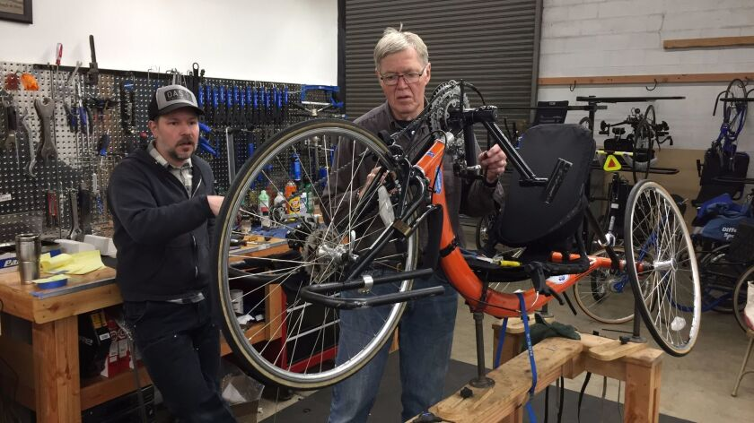 Sherman Coventry, right, works on a hand cycle at the Different Spokes bike shop in Portland, Ore. A