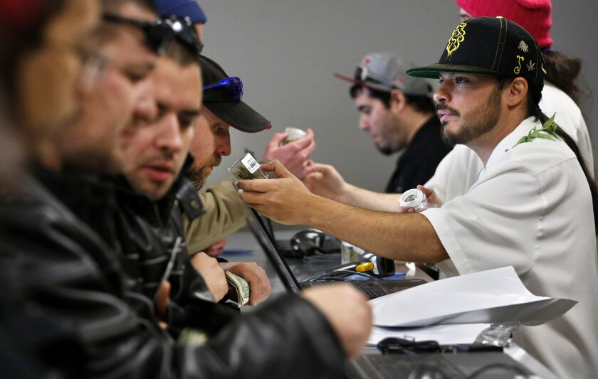 David Marlow, right, helps a customer, who smells a strain of marijuana before buying it, at the crowded sales counter inside a marijuana retail store in Denver on Jan. 1.
