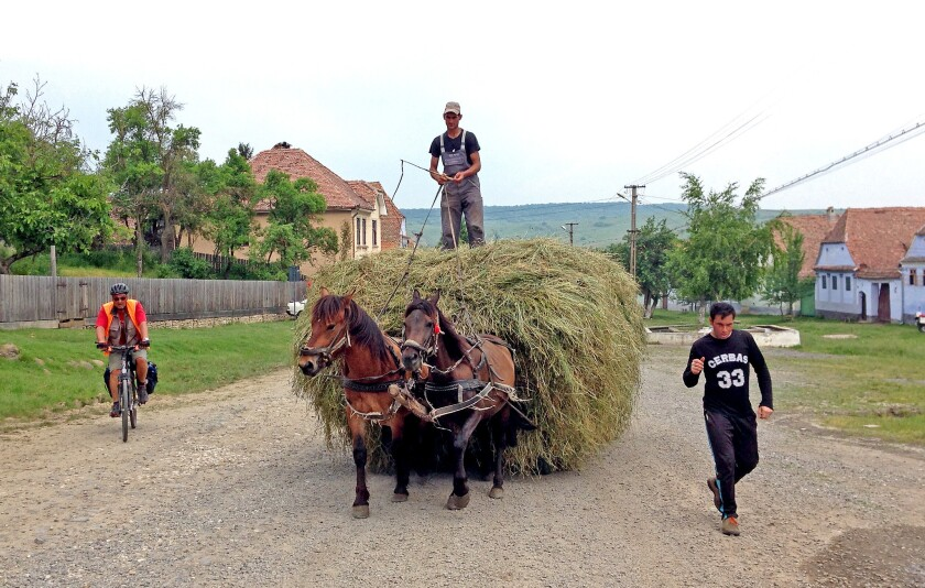A man uses a horse and wagon, still a common form of transportation here, to bring in the hay at one of the rural villages in the Transylvania region of Romania.