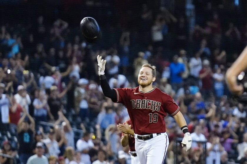 Arizona Diamondbacks' Josh VanMeter smiles as he tosses his helmet in the air as he rounds the bases after his walk-off home run against the Colorado Rockies during the ninth inning of a baseball game Sunday, Oct. 3, 2021, in Phoenix. The Diamondbacks defeated the Rockies 5-4. (AP Photo/Ross D. Franklin)