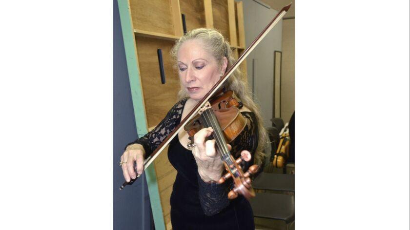 Concertmaster Carolyn Osborn in last minute backstage preparation before last week's season opener