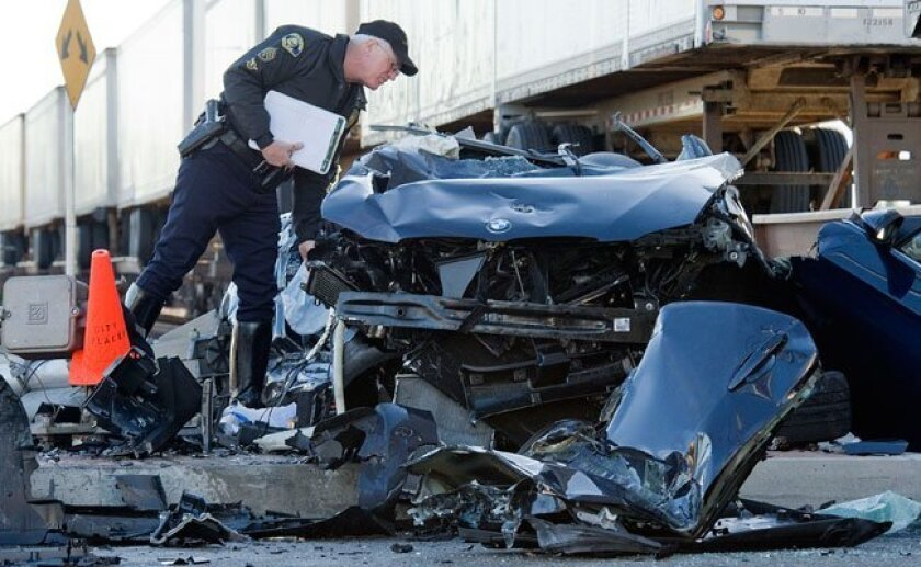 An Anaheim police officer surveys the damage after two men were critically injured when a freight train struck their vehicle in Anaheim, Tuesday morning, Jan 5, 2010.