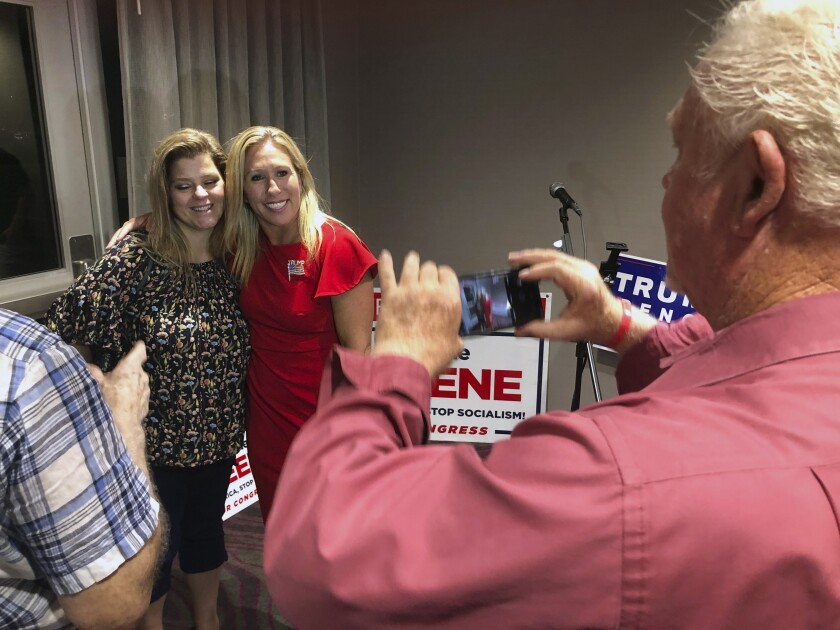 A supporter, left, takes a photo with candidate Marjorie Taylor Greene.