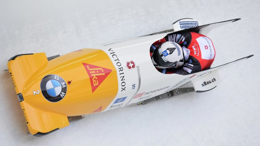 Beat Hefti and Alex Baumann of Switzerland speed down the track  during their third run of the two-man bob race at the Bob World Championships  in Igls, near Innsbruck, Austria, on Sunday, Feb. 14, 2016. (AP Photo/Kerstin Joensson)