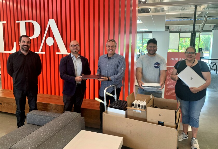 Orange Coast College Architecture Professor Rose Anne Kings, right, receives laptops donated to students by design firm LPA.