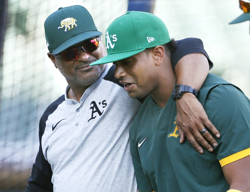 Oakland Athletics assistant hitting coach Eric Martins puts his arm around Khris Davis, right, as they leave the field following batting practice for the team's baseball game against the Detroit Tigers on Wednesday, Sept. 1, 2021, in Detroit. Davis was called up from Triple-A affiliate in Las Vegas for the September roster expansion. (AP Photo/Duane Burleson)