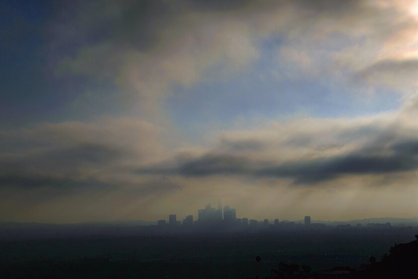 Downtown Los Angeles is shrouded in early morning coastal fog on Friday, Aug. 12, 2016. Southern California was having its smoggiest summer in nearly a decade and hospitals reported an increase of people with breathing problems. (AP Photo/Richard Vogel)