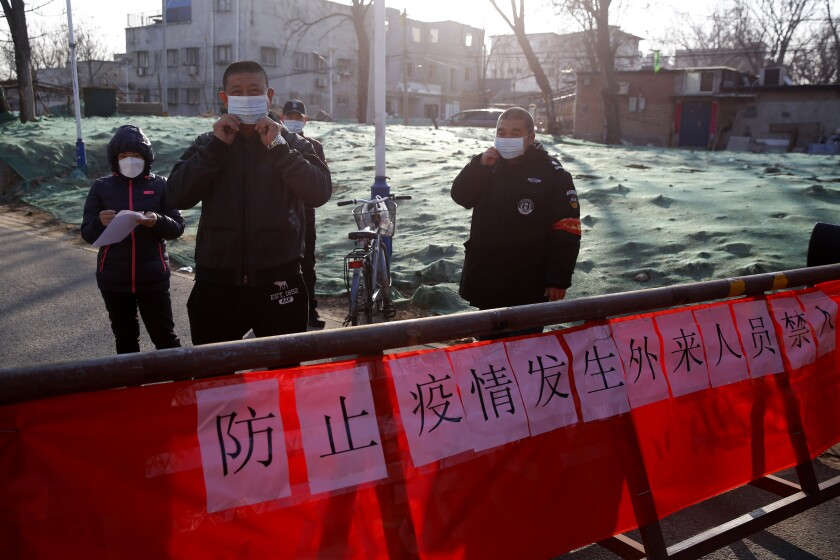 Chinese public security volunteers stand at an entrance their community in Beijing to register personal information of people returning from outside the city.