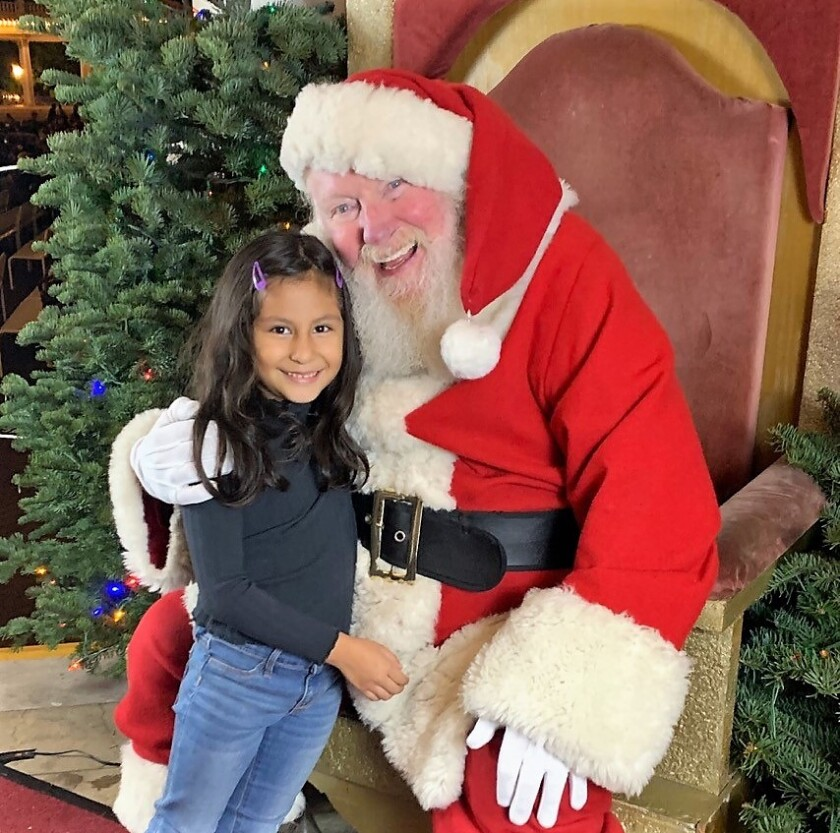 Santa with little girl during Village People concert.jpg
