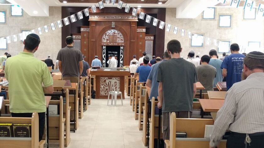 Worshipers take part in an afternoon prayer service at the Beit El Yeshiva.