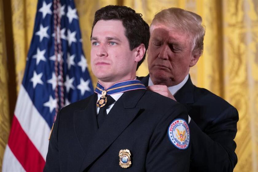 El presidente estadounidense, Donald Trump (d), entrega al Técnico en Emergencias del Escuadrón de Rescate del Condado de Putnam, Sean Ochsenbein (i), una Medalla de Valor de Seguridad Pública durante una ceremonia de premiación hoy, martes 20 de febrero de 2018, en la Sala Este de la Casa Blanca, en Washington, DC (EE.UU.). EFE
