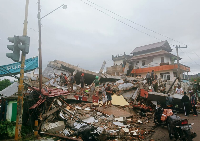 Residents survey damage in Indonesia's West Sulawesi province after Friday's earthquake.