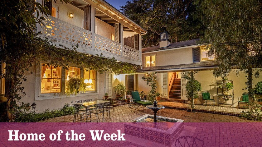 Two wings of the Monterey Colonial-style house, designed by architect Roland E. Coate, surround an inner courtyard with a centerpiece fountain.