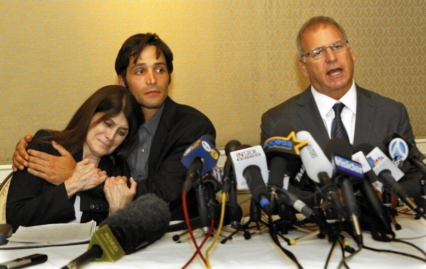 Michael Egan, center, hugs his mother, Bonnie Mound, as attorney Jeffrey Herman announces sexual abuse lawsuits against four Hollywood executives at a news conference in April 2014.