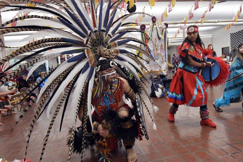 In this Jan. 24, 2020 photo, people in Aztec clothing take part in a dance at the Sagrado Corazon de Jesus church in Minneapolis for a two-day celebration of St. Paul, the patron saint of their Mexican hometown of Axochiapan and nearby villages in the state of Morelos. The celebration is a way to recognize their roots and feel closer to the families and home they left behind. (AP Photo/Jim Mone)