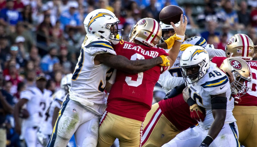 Chargers defensive back Derwin James (33) forces a turnover as he hits 49ers quarterback C.J. Beathard late in the fourth quarter Sunday.