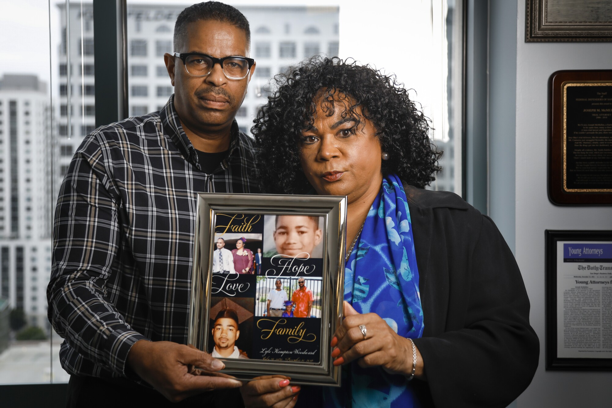 Edward Woodward, left, and his ex-wife, Bessie Woodward, right, hold a framed photo collage of their son, Lyle Woodward, June 26, 2019 in San Diego, California, who died while in San Diego County Jail.
