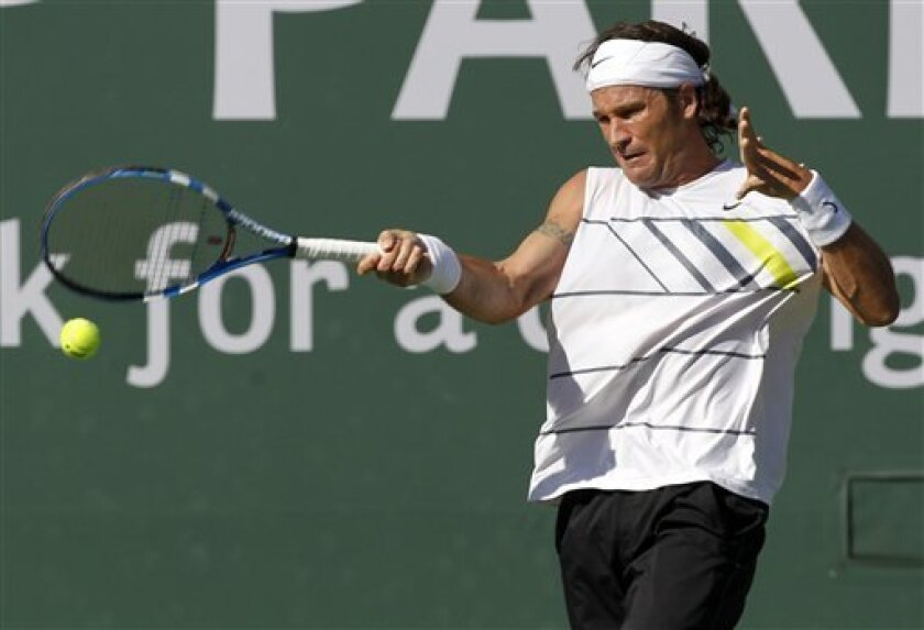 Carlos Moya, of Spain, returns a shot to Tim Smyczek in their match during the BNP Paribas Open tennis tournament in Indian Wells, Calif., Thursday, March 11, 2010. (AP Photo/Chris Carlson)
