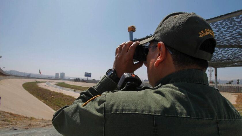A Border Patrol agent uses binoculars to look a man walking in the Tijuana flood control channel at