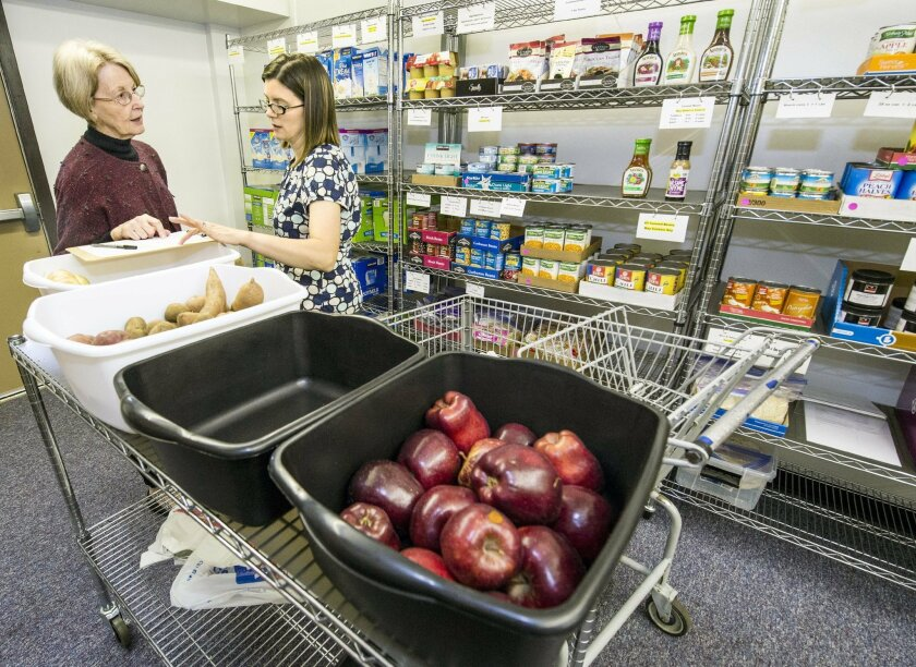 Jan DeMoure, right,looks at a checklist while shopping on Wednesday, May 18, 2016, at the Food Equality Initiative with the assistance of food bank manager, Karen Miller, at the New Haven Seventh-Day Adventist Church in Overland Park, Kansas. The food pantry serves families, like Demoure,  coping w
