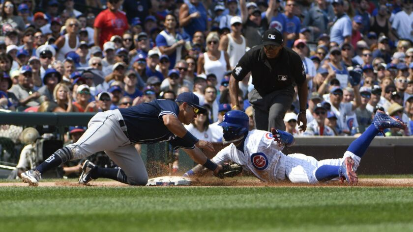 Chicago Cubs' Javier Baez, right, is tagged out on a steal attempt of third base by San Diego Padres
