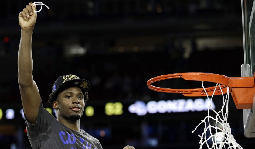 Duke's Justise Winslow holds part of the net after defeating Gonzaga, 66-52, in the NCAA Tournament South Regional final on Sunday.