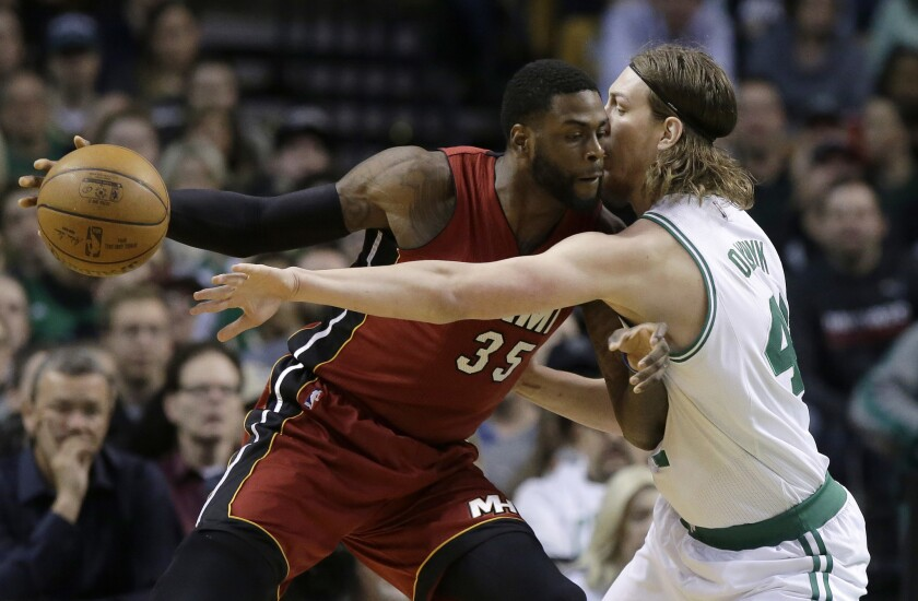 Then-Miami Heat center Willie Reed tries to drive past Boston Celtics center Kelly Olynyk during a game on March 26 in Boston.