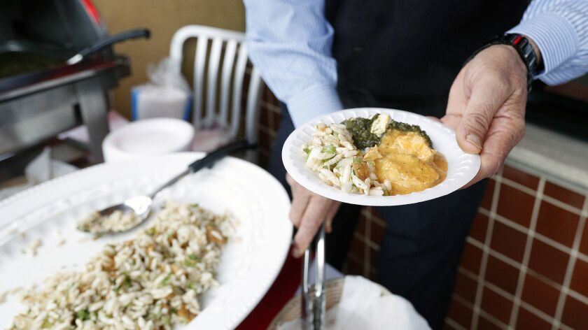 A small plate of Indian food being served by Santokh Singh, owner of All India Cafe at Taste Walk Gl