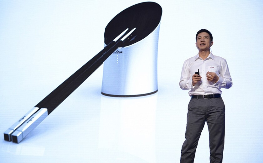"CEO Robin Li introduces Baidu's new ""smart chopsticks"" in Beijing this week."
