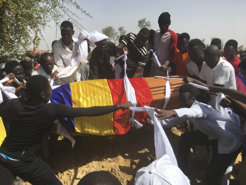 Mourners lower the coffin of one of the victims of protest who was killed this week during his funeral at a cemetery in N'Djamena, Chad, Saturday, May 1, 2021. Hundreds of chanting mourners carrying Chadian flags gathered Saturday to bury victims who were shot dead earlier this week amid demonstrations against the country's new military government .(AP Photo/Sunday Alamba)