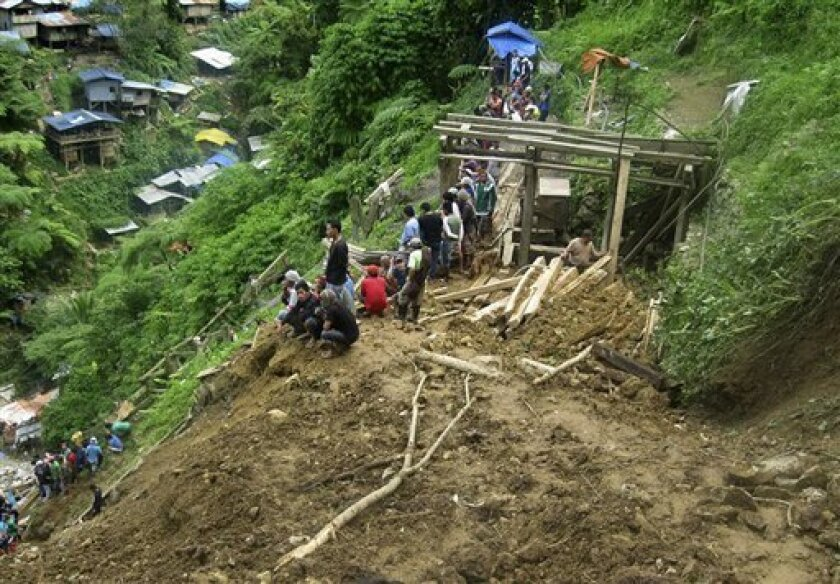 In this photo released by the Philippine Army, residents look at the extent of the damage following a landslide that occurred at the small-scale mining community of Pantukan, Compostela Valley in southern Philippines Thursday Jan. 5, 2012. The landslide tore through a small-scale gold mining site in the southern Philippines on Thursday, months after government officials warned miners that the mountain above them was guaranteed to crumble. (AP Photo/Philippine Army, Senior Police Officer 4 Zoilo Molles Jr.) NO SALES, EDITORIAL USE ONLY