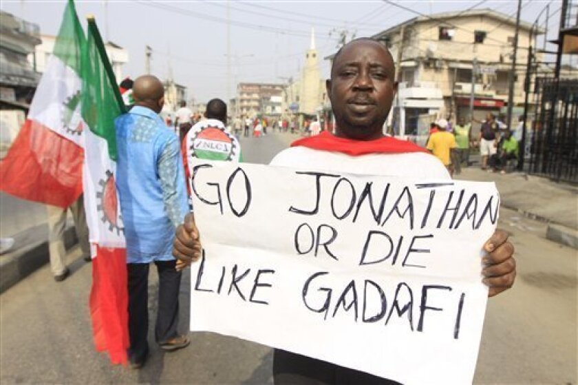 An man protest with a placard saying ' President Jonathan should go or die like Gadafi' on the removal of a fuel subsidy by the government in Lagos, Nigeria, Thursday, Jan. 12, 2012. A union representing 20,000 oil and gas workers in Nigeria threatened Thursday it would shut down all production starting Sunday to take part in the crippling nationwide strike over spiraling fuel prices. (AP Photo/Sunday Alamba)