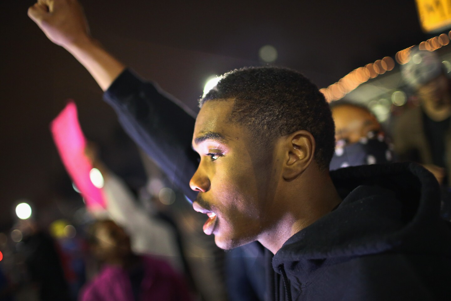 Demonstrators protest in front of the police station in Ferguson, Mo.