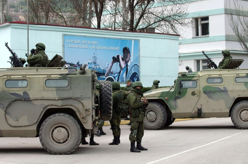 Unidentified armed individuals with armored vehicles block the base of the Ukrainian border guard service in Sevastopol over the weekend.