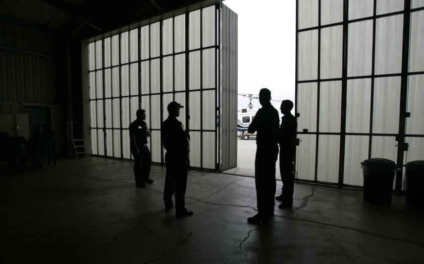 After a news conference yesterday, a group from Cal Fire met in a hangar at the Ramona airport.