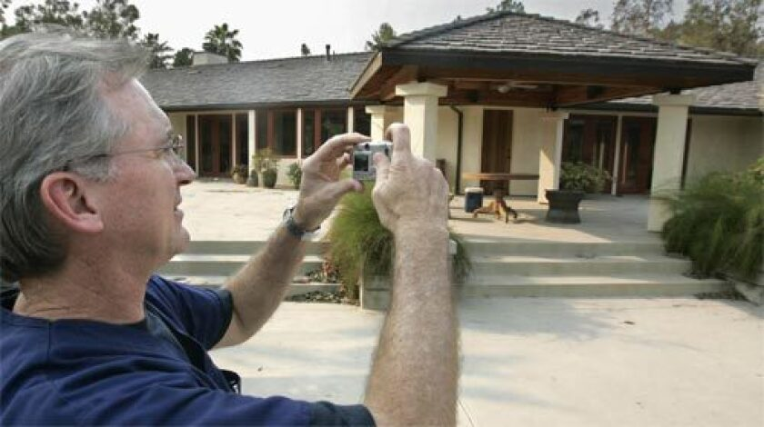 SURVIVOR: Dr. David Roland takes a snapshot of his house in Rancho Santa Fe, Calif., which had been sprayed with fire retardant by a private firm and emerged from the flames intact.