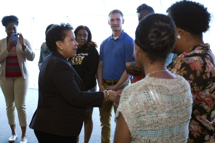 Atty. Gen. Loretta Lynch shakes hands with students before meeting with members of Congress and faith leaders at the University of Baltimore on Tuesday, May 5, 2015, in Baltimore.
