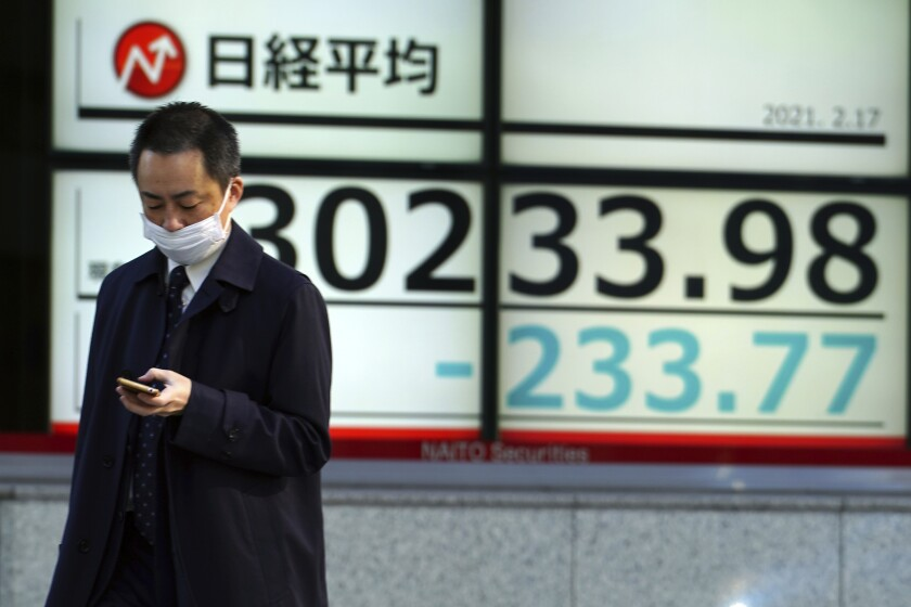 A man wearing a protective mask walks in front of an electronic stock board showing Japan's Nikkei 225 index at a securities firm Wednesday, Feb. 17, 2021, in Tokyo. Asian shares were lower Wednesday as investors sold to lock in profits from the recent rally driven by hopes economies will gradually return to a pre-pandemic normal. (AP Photo/Eugene Hoshiko)