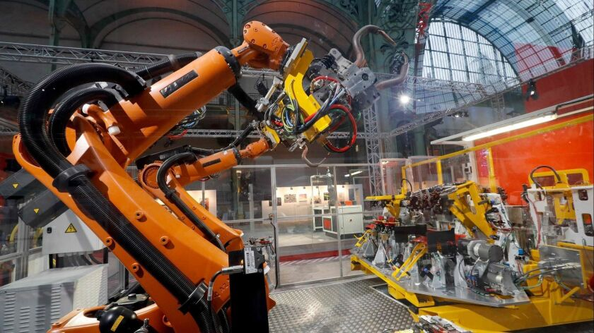 """An assembly line robot at the """"Extraordinary Factory"""" exhibition at Paris' Grand Palais in November."""