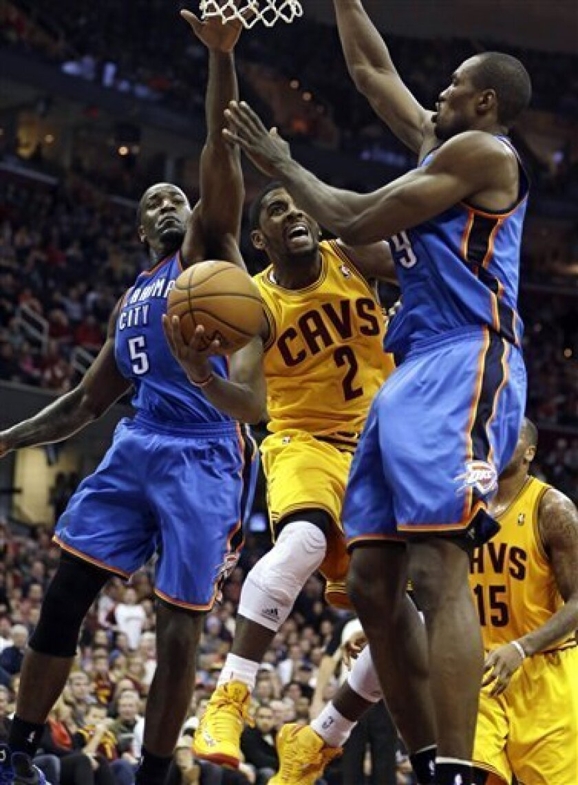 Cleveland Cavaliers' Kyrie Irving (2) shoots to the basket against Oklahoma City Thunder's Kendrick Perkins (5) and Serge Ibaka (9), from the Republic of Congo, during the fourth quarter of an NBA basketball game on Saturday, Feb. 2, 2013, in Cleveland. The Cavaliers won 115-110. (AP Photo/Tony Dej