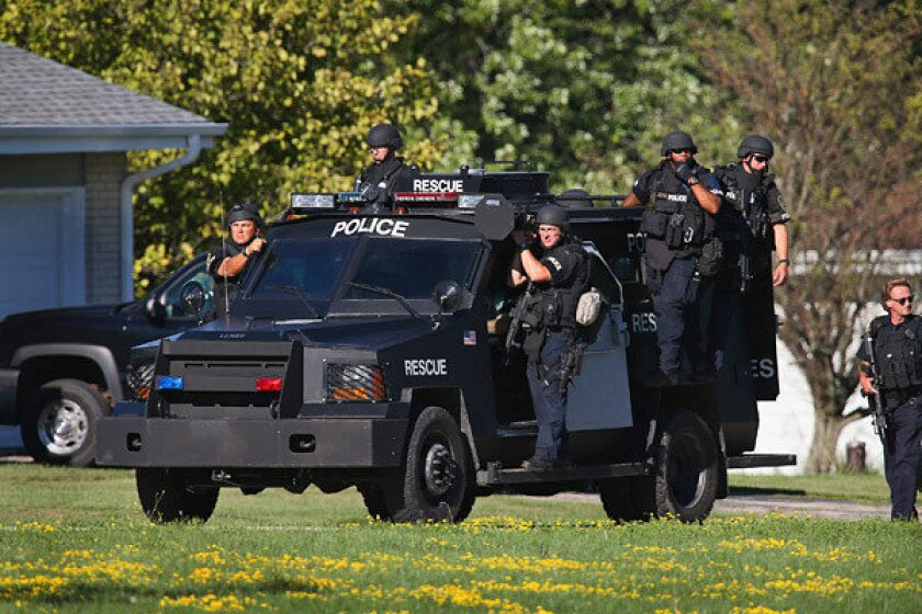 Police work outside the Sikh Temple of Wisconsin where a suspected gunman stormed the mass and opened fire, killing six and injuring three, including the police officer who then shot the gunman dead.