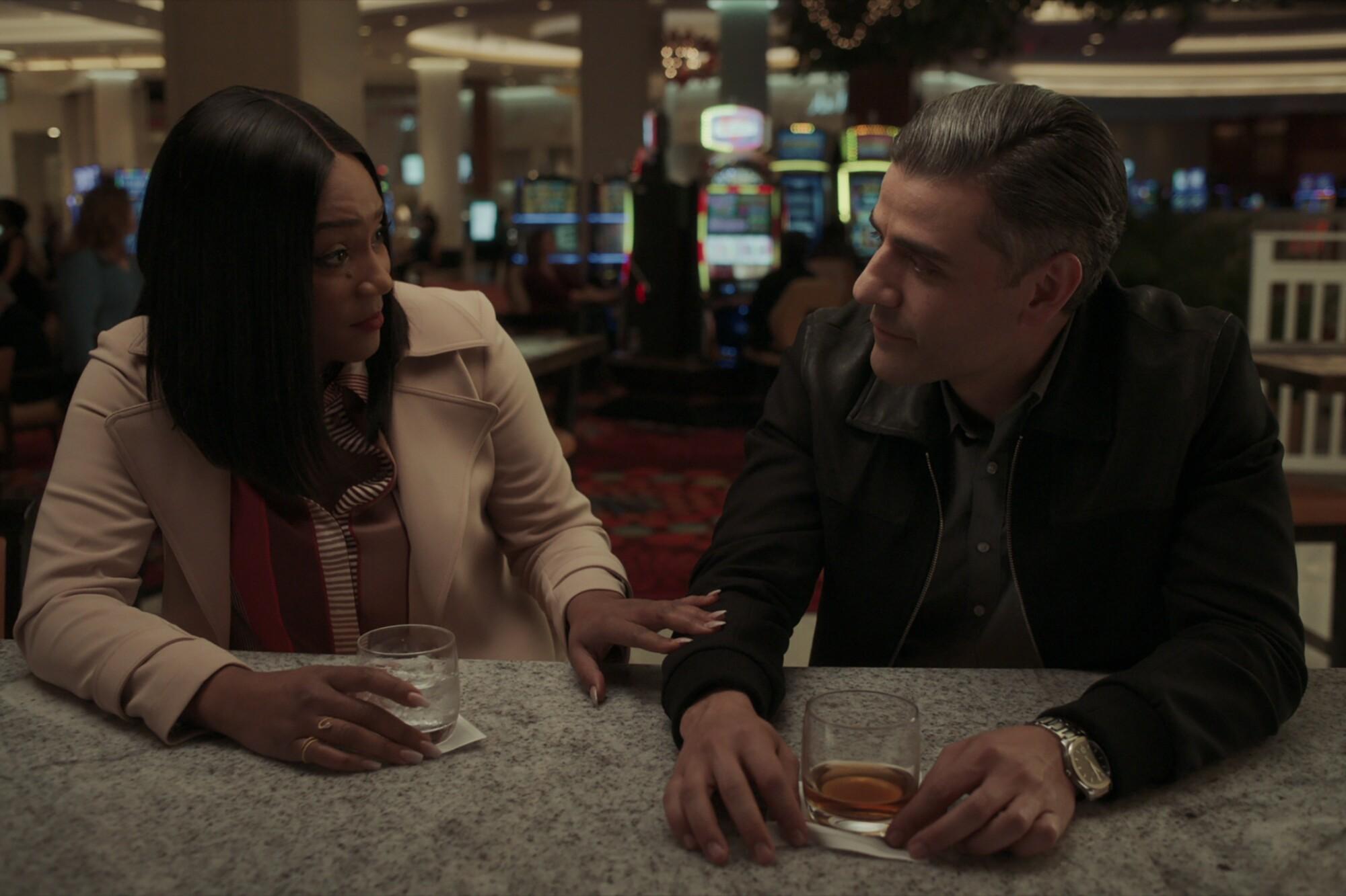 Tiffany Haddish and Oscar Isaac sit at a bar holding drinks