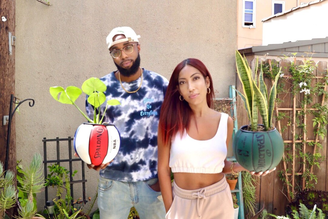 Justin Cox and Karissa Allen hold Spalding basketballs with plants inside.