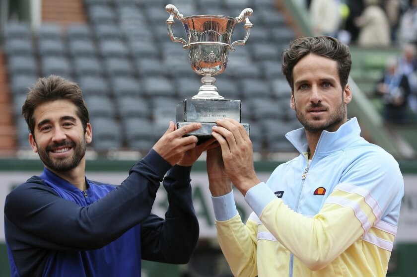 Spanish pair Feliciano Lopez, right, and Marc Lopez hold their trophy after winning the men's doubles final match of the French Open tennis tournament against Bob and Mike Bryan, of the U.S,  at the Roland Garros stadium, Saturday, June 4, 2016 in Paris.  (AP Photo/David Vincent2