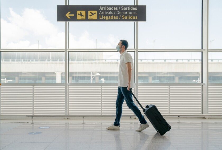 A stock photo of a man travelling with face masks for COVID-19