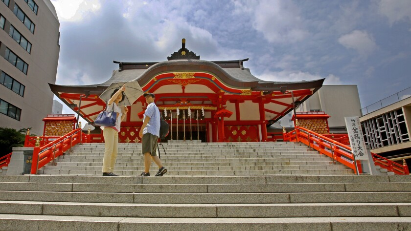 A couple chats in front of the main hall of Hanazono Shrine in Tokyo. A round-trip fare from mid-August to early December puts Japan's capital within reach.