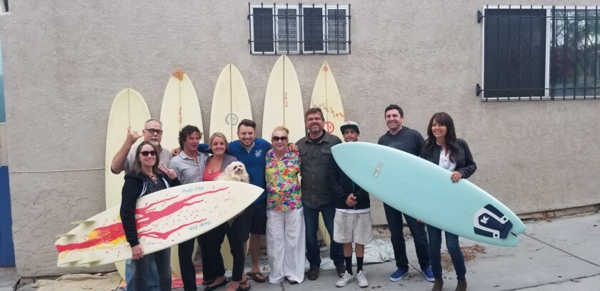 TextEditor OB Town Council Board poses with the surf boards donated by the late Nathan Margolis: Jill Kent, Daniel Grofer, Scott Grace, Marin Green, Corey Bruins, Trudy Levenson, Mark Winkie, Isaac Darby, Jon Carr and Stacie Woehrle