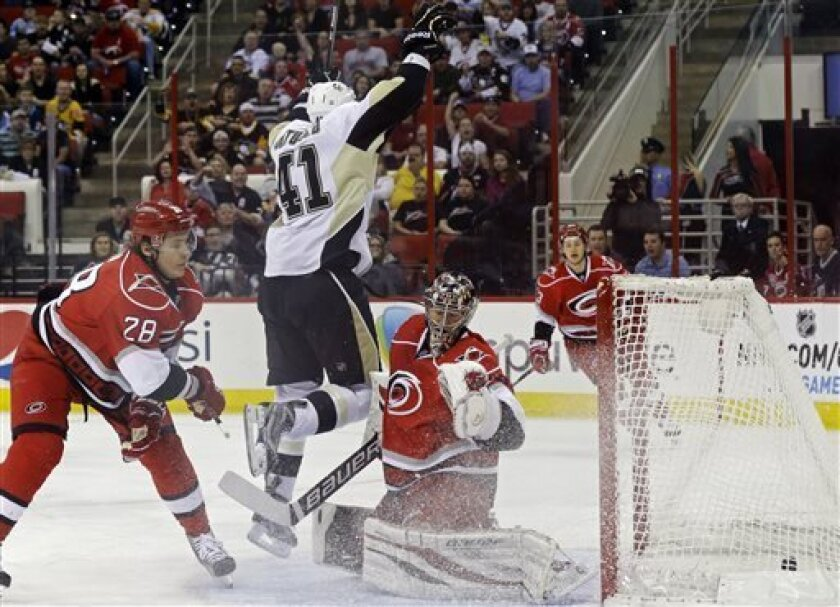 Carolina Hurricanes' Alexander Semin (28), of Russia, and goalie Justin Peters (35) defend as Pittsburgh Penguins' Robert Bortuzzo (41) reacts to his goal during the first period of an NHL hockey game in Raleigh, N.C., Tuesday, April 9, 2013. (AP Photo/Gerry Broome)